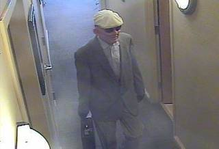Surveillance photo a bank robbery suspect. The man was described as being about 5 feet 7 inches to 5 feet 9 inches tall, of medium build and wearing a mask depicting an older white man. Photo provided by the FBI - Provided by the FBI