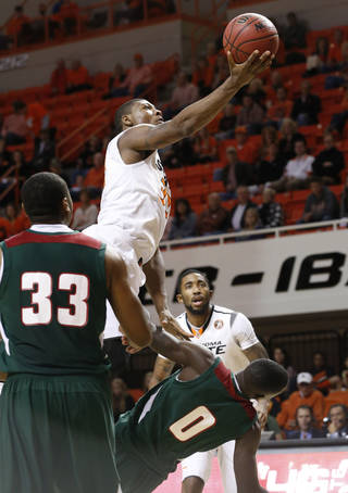 Oklahoma State guard Marcus Smart is fouled by Mississippi Valley State forward Vacha Vaughn (0) as he shoots in the second half of an NCAA college basketball game in Stillwater, Okla., Friday, Nov. 8, 2013. Oklahoma State won 117-62. At right is Oklahoma post Michael Cobbins. (AP Photo/Sue Ogrocki)