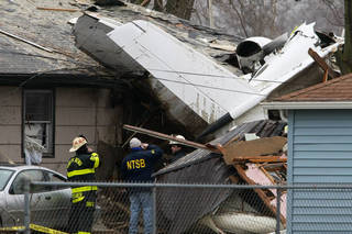 A National Transportation Safety Board investigator and South Bend firefighters early Monday, March 18, 2013, survey the scene of Sunday's fatal plane crash, along Iowa Street in South Bend, Ind. Photo by James Brosher, South Bend Tribune/AP James Brosher - AP