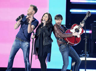 From left, Charles Kelley, Hillary Scott and Dave Haywood, of musical group Lady Antebellum, perform at the 48th Annual Academy of Country Music Awards at the MGM Grand Garden Arena in Las Vegas on Sunday, April 7, 2013. (Photo by Chris Pizzello/Invision/AP) ORG XMIT: NVPM232