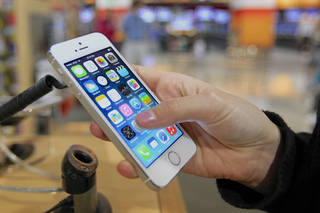 A customer examines a new iPhone 5s at the Nebraska Furniture Mart in Omaha, Neb., on Friday, Sept. 20, 2013, the day the new iPhone 5c and 5s models go on sale. (AP Photo/Nati Harnik) ORG XMIT: NENH102
