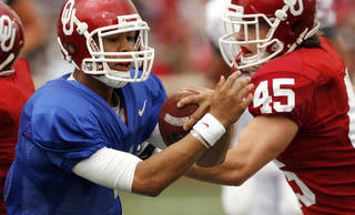 Quarterback Kendal Thompson keeps the ball and is challenged by Caleb Gastelum (45) during the OU football team's annual Red and White Game at Gaylord Family - Oklahoma Memorial Stadium on Saturday, April 14, 2012, in Norman, Okla. Photo by Steve Sisney, The Oklahoman