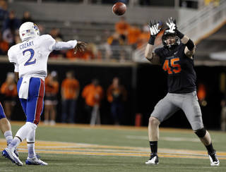 Oklahoma State's Caleb Lavey, right, prepares to block a pass by Kansas' Montell Cozart during Saturday's game in Stillwater. Lavey led the Cowboys with nine tackles in Saturday's 42-6 victory.Photo by Sarah Phipps, The Oklahoman