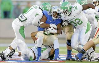 Tulsa's Ja'Terian Douglas is stopped by Zed Evans(1), Jamal Mashall(14) and Fred Scott of North Texas on Nov. 30, 2013. MIKE SIMONS/Tulsa World file