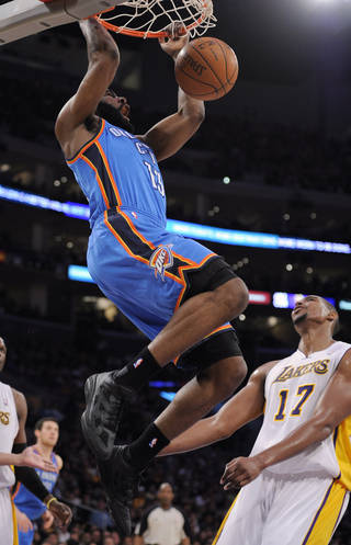 Oklahoma City Thunder guard James Harden, left, dunks as Los Angeles Lakers center Andrew Bynum looks on during the first half of an NBA basketball game Sunday, April 10, 2011, in Los Angeles. (AP Photo/Mark J. Terrill)