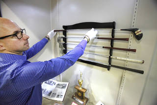 """Exhibit coordinator Derek Lee places one of Danny Edwards' clubs on a rack for display at the Edmond Historical Society and Museum. The new exhibit, """"Fore - Looking Back at Golf in Edmond"""" is open through Sept. 27. PHOTO BY DAVID MCDANIEL, THE OKLAHOMAN David McDaniel - The Oklahoman"""