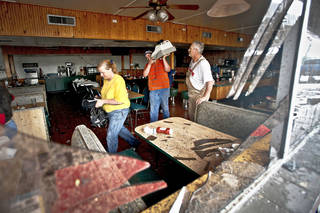 Seen through a broken window, employees gather valuables from the inside of the Anderson Travel Plaza after a tornado damaged the area Monday around Interstate 40 and Choctaw Road in Oklahoma City. Photo by Chris Landsberger, The Oklahoman