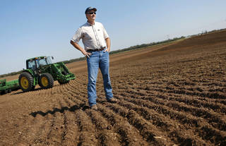 David Harman, of El Reno, stands Wednesday in one of the Canadian County fields where he planted wheat. He said recent rains allowed him to do so. The U.S. Drought Monitor report released Thursday shows 99.71 percent of Oklahoma remains in severe to exceptional drought. However, the percentage in the worst category has fallen significantly. Story, Page 11A. Photo by Jim Beckel, THE OKLAHOMAN