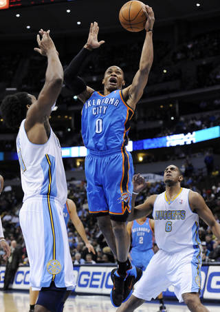 Oklahoma City Thunder guard Russell Westbrook (0) goes up for a shot against Denver Nuggets center Nene Hilario (31) from Brazil and Arron Afflalo (6) during the first quarter of an NBA basketball game Wednesday, Jan. 19, 2011, in Denver. (AP Photo/Jack Dempsey)