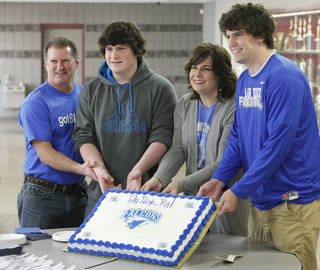 Edmond Memorial football player Ry Huff, right, poses for a photo with a cake and his father Darren, brother Denton, 14, and mom Deana before signing with Air Force, Wednesday, February 1, 2012. Photo by David McDaniel, The Oklahoman
