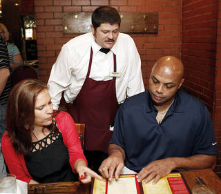 Michael Sharp, a server at Cattlemen's Steakhouse, stands and discusses the menu Friday with former NBA player and TNT analyst Charles Barkley, right, as Elly Trickett, executive editor of weightwatchers.com, gives Barkley advice on what to order at Cattlemen's Steakhouse during a tour of Oklahoma City. Photo by Nate Billings, The Oklahoman