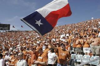 University of Texas fan Ernest Anguiano of Austin, Texas, waves a Texas state flag before the start of the annual Texas/Oklahoma college football game, Saturday, Oct. 7, 2006. (AP Photo/Ron Heflin)