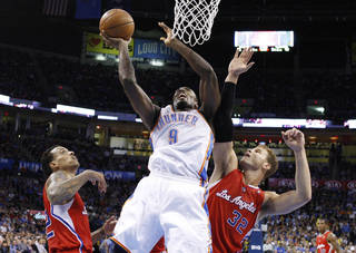 Oklahoma City Thunder forward Serge Ibaka (9) shoots between Los Angeles Clippers forwards Matt Barnes, left, and Blake Griffin (32) in the second quarter of an NBA basketball game in Oklahoma City, Wednesday, Nov. 21, 2012. Oklahoma City won in overtime, 117-111. (AP Photo/Sue Ogrocki) ORG XMIT: OKSO113
