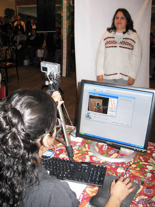 A Mexican national living in Oklahoma gets her photo taken for a Meixcan ID card Saturday morning at Chelino's restaurant in Oklahoma City. PHOTO BY JOHNNY JOHNSON, THE OKLAHOMAN