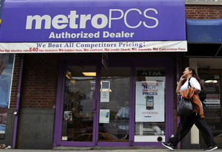 A pedestrian talks on a cellular phone Wednesday as he walks past a MetroPCS authorized dealer in New York. AP Photo Mary Altaffer