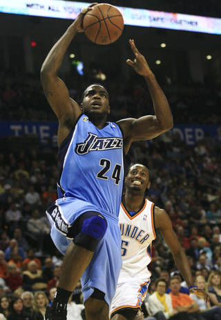 Utah Jazz forward Paul Millsap, left, goes to the basket in front of Oklahoma City Thunder guard Kyle Weaver, right, in the second quarter of an NBA basketball game in Oklahoma City, Friday, March 20, 2009. (AP Photo/Sue Ogrocki)