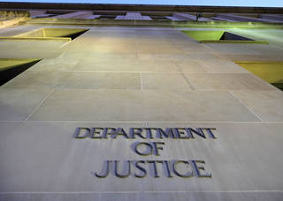 An entrance is shown to the Justice Department in Washington. The federal panel that sets sentencing policy eased penalties this year for potentially tens of thousands of drug prisoners. AP File Photo J. David Ake - AP