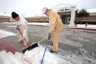 Lead Custodian Miran Johnson and grounds worker Kermit Walker clears snow and ice from the walkway at Thelma Parks Elementary School in preparation for school reopening tomorrow, Monday, December, 9, 2013. Photo by David McDaniel, The Oklahoman