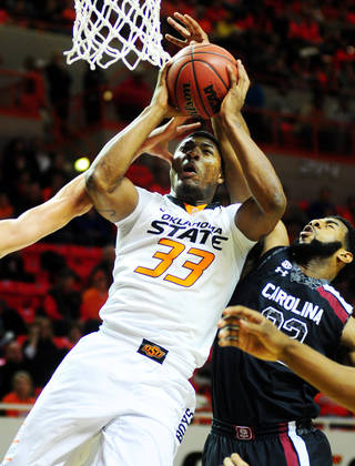 Oklahoma State sophomore guard Marcus Smart is fouled while attempting a dunk over a South Carolina defender during Friday's game. Photo by KT King, For the Tulsa World