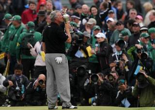 Northern Ireland's Darren Clarke kisses the Claret Jug trophy in front of the world's media as he celebrates winning the British Open Golf Championship at Royal St George's golf course Sandwich, England, Sunday, July 17, 2011. ( (AP Photo/Tim Hales) ORG XMIT: XSDW350 Tim Hales - AP