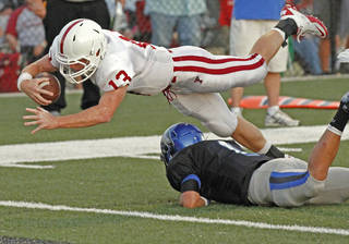 Tuttle quarterback Cooper Koons (13) scores on a keeper over Newcastle's Cade Nichols in the first quarter as the Newcastle Racers play the Tuttle Tigers in high school football on Friday, September 9, 2011, in Newcastle, Okla. Photo by Steve Sisney, The Oklahoman