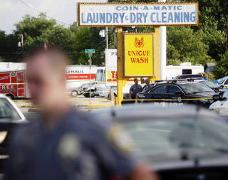 Officers surround the scene of an officer involved shooting Thursday that happened at the Coin-A-Matic Laundry & Dry Cleaning at the intersections of 17th street and Portland Avenue. Photo by KT King, The Oklahoman KT King -