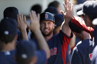 Boston Red Sox Corey Brown is greeted in the dugout after scoring on a two-run RBI double by Dustin Pedroia in the fifth inning of an exhibition baseball game against the Minnesota Twins in Fort Myers, Fla., Thursday, March 13, 2014. The Red Sox won 4-3. (AP Photo/Gerald Herbert)