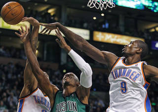 Oklahoma City Thunder forward Serge Ibaka (9) and guard Thabo Sefolosha, left, stop Boston Celtics guard Ray Allen (20) on a drive to the basket in the first quarter of an NBA basketball game in Boston, Monday, Jan. 16, 2012. (AP Photo/Charles Krupa)