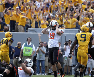 OSU / REACTION: Oklahoma State's Ben Grogan (19) reacts after missing a tying field goal late in the fourth quarter of a college football game between Oklahoma State University and West Virginia University on Mountaineer Field at Milan Puskar Stadium in Morgantown, W. Va., Saturday, Sept. 28, 2013. Photo by Sarah Phipps, The Oklahoman