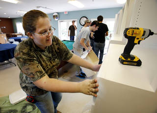 Moore Norman Technology Center student Brianna Rusgrove gets ready to install a dresser and bookshelf in an apartment at Bridges. PHOTO BY STEVE SISNEY, THE OKLAHOMAN STEVE SISNEY
