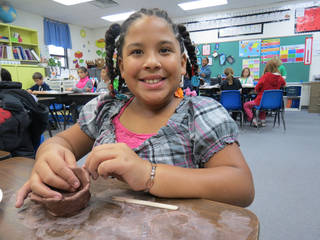 Edmond's Ida Freeman Elementary third-grader Jabrena Baysinger sculpted clay during a lesson on the artifacts of Oklahoma's Spiro Mounds. PHOTO PROVIDED. - PHOTO PROVIDED