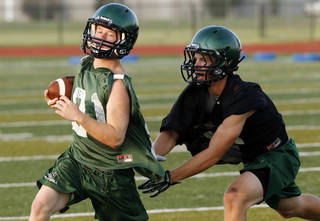 Ben Jones, left, carries during Norman North High School football practice on Thursday in Norman. Photo by Steve Sisney, The Oklahoman