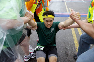 Andrew Hwang is helped up after finishing the Oklahoma City Memorial Marathon in Oklahoma City, Sunday, April 29, 2012. Photo by Bryan Terry, The Oklahoman