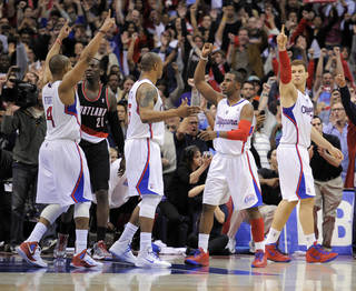 Los Angeles Clippers guard Randy Foye, left, celebrates as time runs out with teammates forward Caron Butler, third from left, guard Chris Paul, second from right, and forward Blake Griffin, right, as Portland Trail Blazers forward J.J. Hickson looks on in their NBA basketball game, Friday, March 30, 2012, in Los Angeles. The Clippers won 98-97. (AP Photo/Mark J. Terrill) ORG XMIT: LAS113