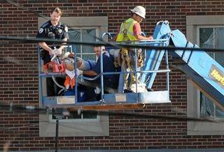 Norman, Okla., fire personnel stablize a construction worker Monday, June 18, 2012 in Norman, Okla., as an aerial platform lowers them to the ground. The unidentified worker fell from the top of the four-story Headington Hall being constructed on the University of Oklahoma campus. The victim later died. (AP Photo/The Norman Transcript, Jerry Laizure)