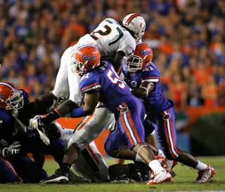Brandon Spikes and Ryan Stamper stop Graig Cooper from getting a first down during the third quarter of the University of Florida vs University of Miami game at Florida Field Sept. 6, 2008. ( Brandon Kruse/The Gainesville Sun )