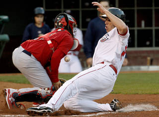 Oklahoma City's Mike Hessman slides past Memphis' Steven Hill to score in the first inning of a baseball game between the Oklahoma City RedHawks and the Memphis Redbirds at Chickasaw Bricktown Ballpark in Oklahoma City, Saturday, April 7, 2012. Photo by Bryan Terry, The Oklahoman