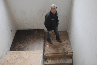 Mike Hancock of Basement Contractors Inc. walks down to a basement in a home that his company is working on in the Creek Bend addition in Edmond. KT King - The Oklahoman