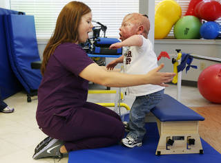 Melanie Connel, a physical therapist, works with Fletcher Burns, 8, at the Children's Center in Bethany. Photo by Nate Billings, The Oklahoman NATE BILLINGS - NATE BILLINGS