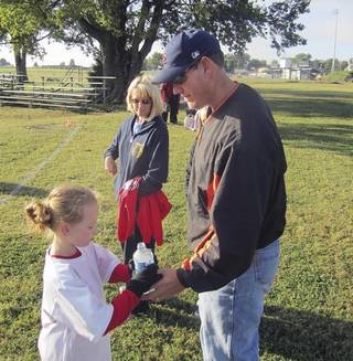 Abby York, 6, gets a drink from her dad, Allen York, during a break in a recent soccer game. (Muskogee Phoenix photo)