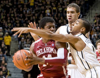 Oklahoma's Carl Blair, left, is surrounded by Missouri's Phil Pressey, right, and Justin Safford, rear, on Saturday. AP photo