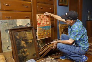 Max Hester holds an old promotional poster for a Kiwanis Club carnival in Nicoma Park. Hester has been searching through numerous items piled against a wall in the upstairs hallway of his parents' home in Choctaw. Photo by Jim Beckel, The Oklahoman Jim Beckel