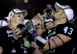 TCU quarterback Andy Dalton, left, holds the Rose Bowl trophy while TCU linebacker Tank Carder, right, kisses it after the Horned Frogs beat Wisconsin on Saturday. AP photo