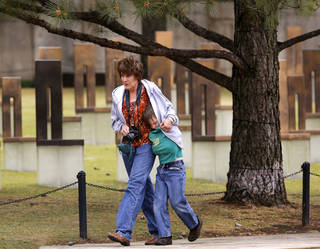 Wendy Lindsey huddles with her son, Weston, 7, covering him with her jacket while visiting the memorial Thursday morning. Wendy brought Weston and another son, Morgan, to the memorial during a visit to Oklahoma City from their home in Lincoln, AR. Predicted cold temperatures and other weather factors prompted officials to move Friday's ceremony commemorating the 18th anniversary of the bombing of the Murrah Federal Building to an indoor venue near the Oklahoma City National Memorial in downtown Oklahoma City. Photo by Jim Beckel, The Oklahoman. Jim Beckel - THE OKLAHOMAN