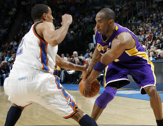 Thabo Sefolosha, left, tries to knock the ball away from Los Angeles' Kobe Bryant during OKC's 91-75 win Friday. PHOTO BY NATE BILLINGS, THE OKLAHOMAN