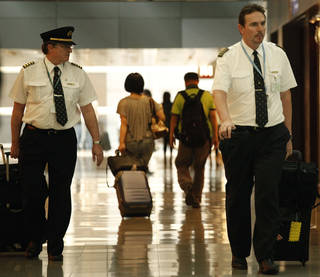 Two pilots from Cathay Pacific walk in the Hong Kong International Airport in Hong Kong. The U.S. airline industry will need to hire 1,900 to 4,500 new pilots annually over the next 10 years due to an expected surge in retirements of pilots. AP File Photo Vincent Yu - AP