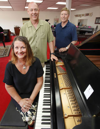 Albert Evans' children Elaine Evans Walters, Phillip Evans, left, and Steve Evans surround a restored 1911 Baldwin piano at their late father's store at 4100 N MacArthur Blvd. Auctioneer Louis Dakil will sell the real estate and liquidate the inventory at auctions on Saturday at his warehouse, 200 NW 114. Steve Gooch - The Oklahoman