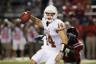 Texas quarterback David Ash (14) fights through an attempted tackle by Mississippi defensive end Channing Ward (11) in the second quarter of their NCAA college football game in Oxford, Miss., Saturday, Sept. 15, 2012. Texas won 66-31. (AP Photo/Rogelio V. Solis) ORG XMIT: MSRS124