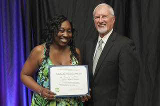 Michelle Thomas-Watt receives recognition from Ed Lake, Department of Human Services director. PHOTO PROVIDED