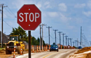 A stop sign stands in the middle of the continued work on a road expansion project near NW 164th and Penn Ave. on Wednesday, Oct. 2, 2013 in Edmond, Okla. Photo by Chris Landsberger, The Oklahoman